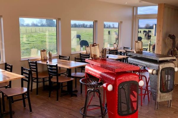 Interior of cafe with two feature tables that are tractor bonnets